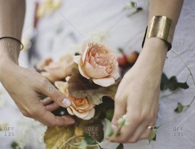A woman arranging fresh flowers on a tabletop covered with a white cloth