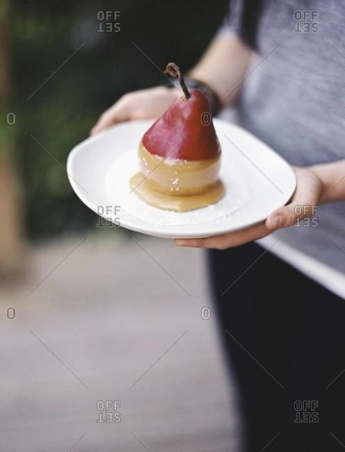 A woman holding a plate with a dessert of fresh organic pear dipped in fudge sauce