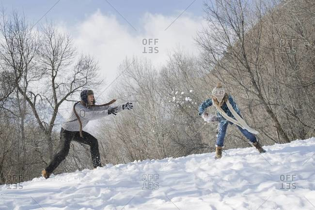 A father and daughter having a snowball fight