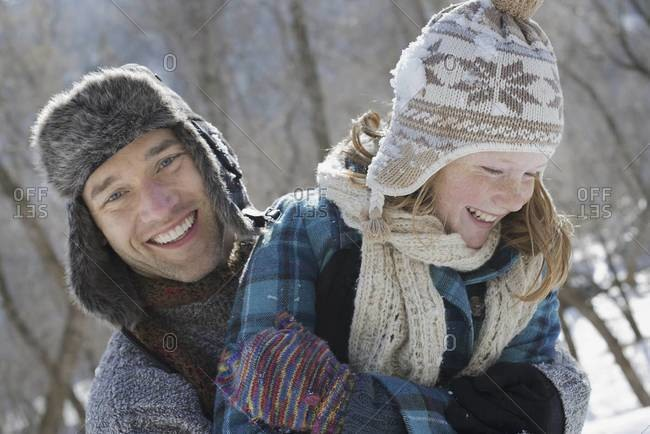 A young girl with a bobble hat and scarf and a man hugging her