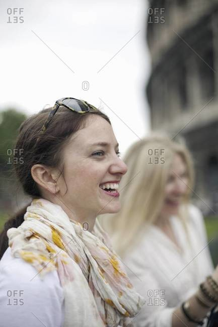 Two women standing outside the Colosseum Roman amphitheater in Rome, side by side