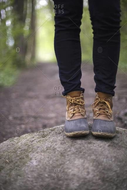 A woman wearing walking boots and jeans, standing on a stone beside a path in woodland