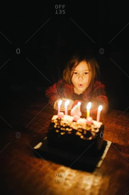 Young girl blowing out candles on birthday cake