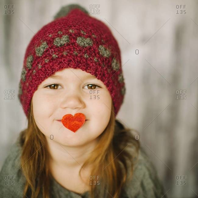 Portrait of a young girl with a love heart in her mouth