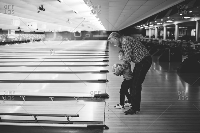 Young girl bowling with her Grandfather