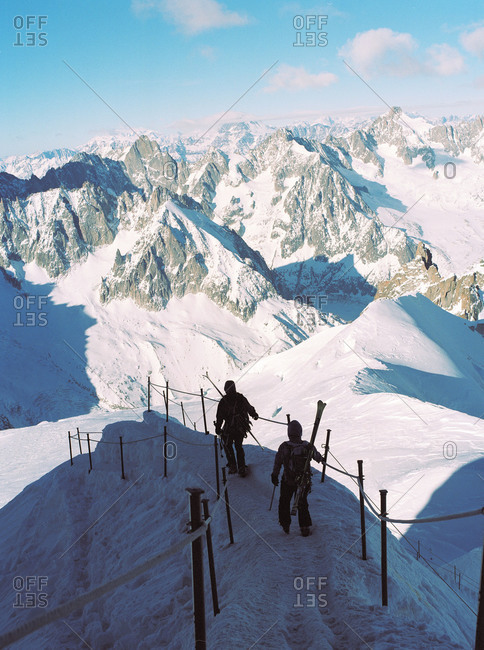 Two skiers walking down a slope