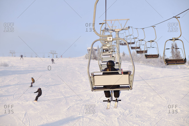 Back view of a man riding the chairlift