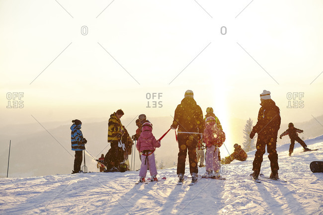 Skiers standing at the top of a slope
