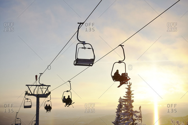 People riding the chairlift at sunset