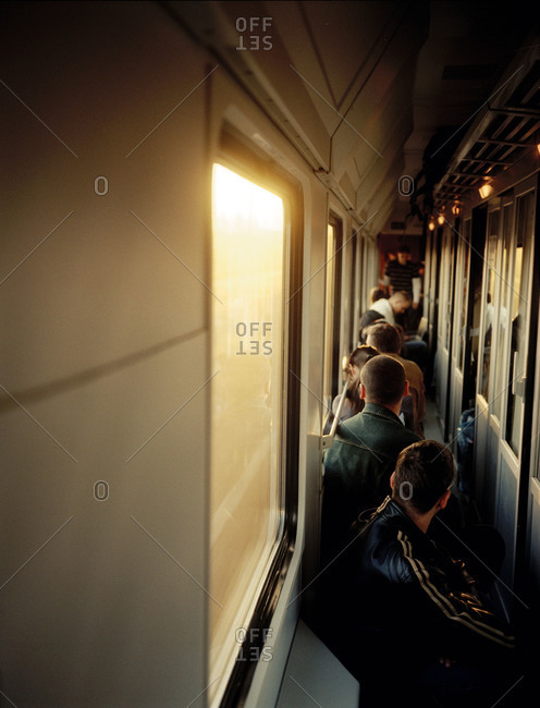 Passengers sitting in the hallway of a train
