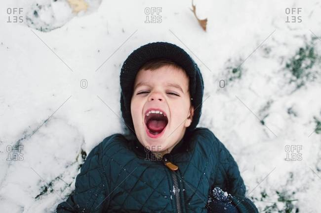 Boy laughs in snow