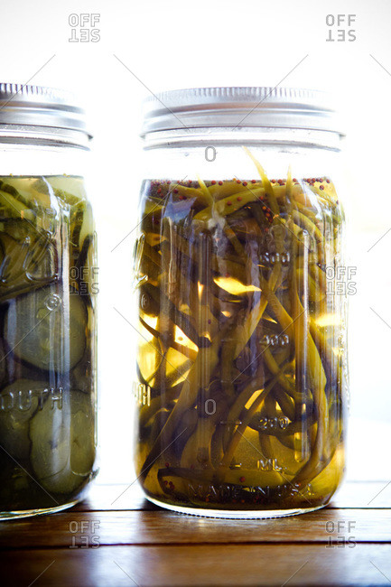 Jars of pickled cucumbers and garlic scapes
