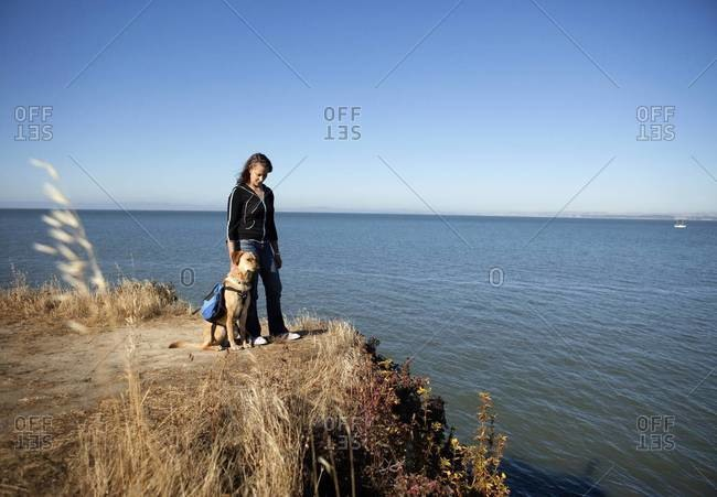 Woman and her dog standing on cliff