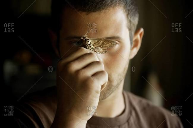 Young man holding moth over his face