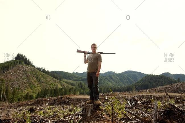 Man posing with shotgun on deforested area