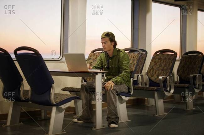 Young man working on laptop on ferry