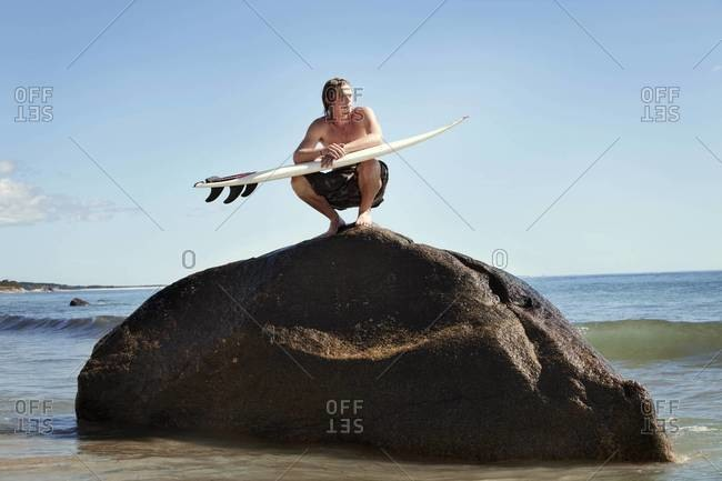 Surfer squatting on rock and waiting for waves