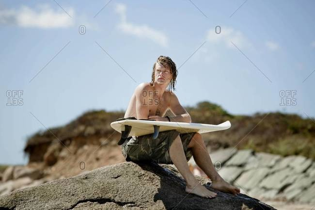 Surfer resting on rocks