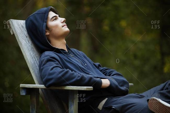 Young man relaxing in chair outdoors