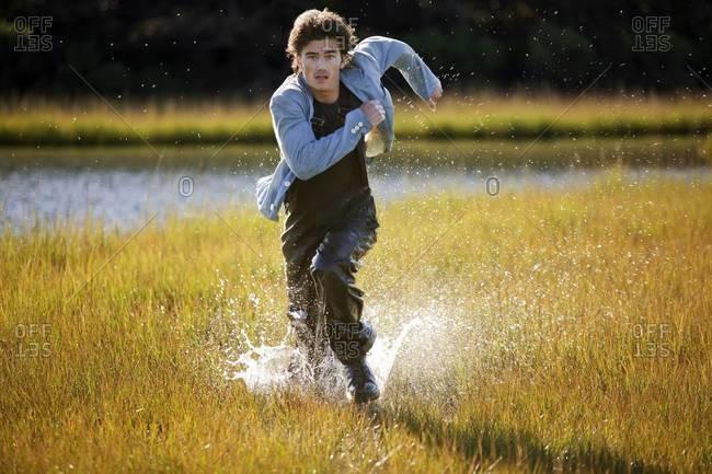 Man running through marsh