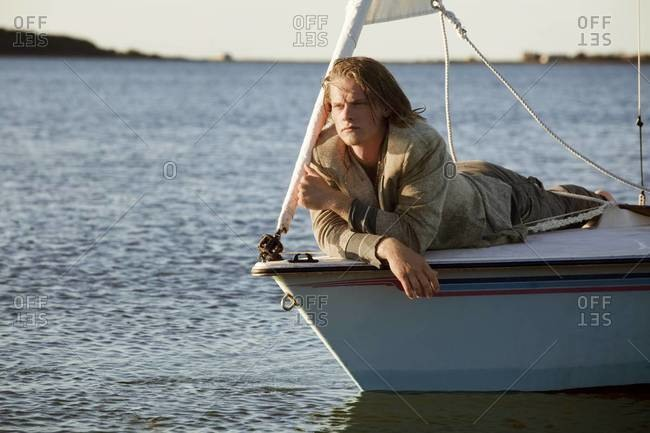 Young man lying on bow of sailboat