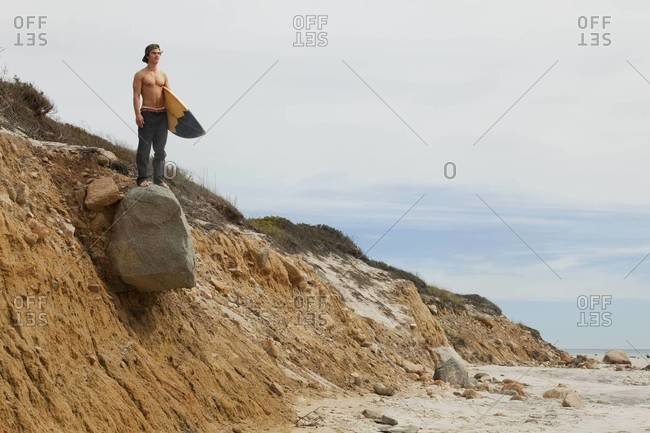 Surfer standing on rocky bluff and watching surf