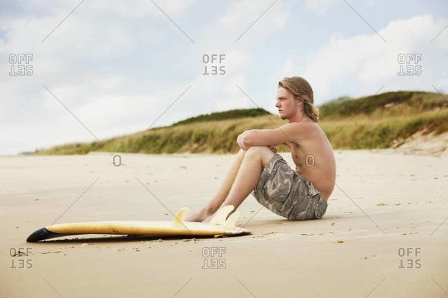 Surfer sitting on sandy beach and watching surf