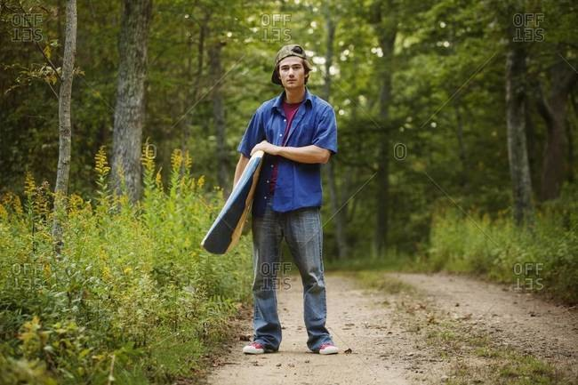 Young man standing with surfboard on path