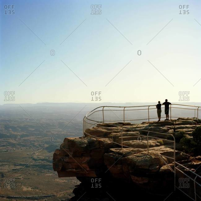 Couple standing at edge of Grand Canyon