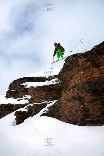 Extreme skier jumping off ledge in Vail, Colorado