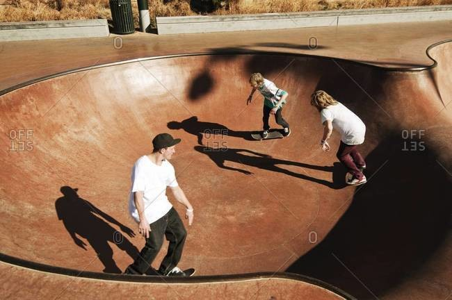 Skateboarders circle around in a pool