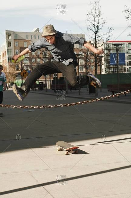 Skateboarder jumping over a chain