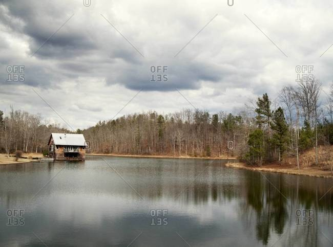 Boathouse on a lake under storm clouds