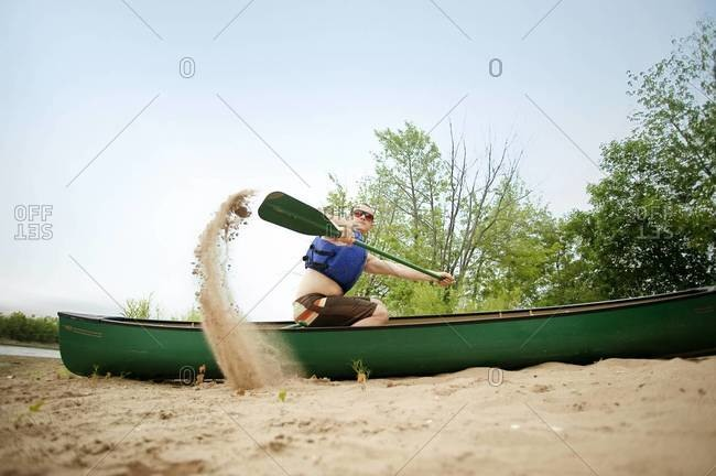 Young man paddling a beached canoe