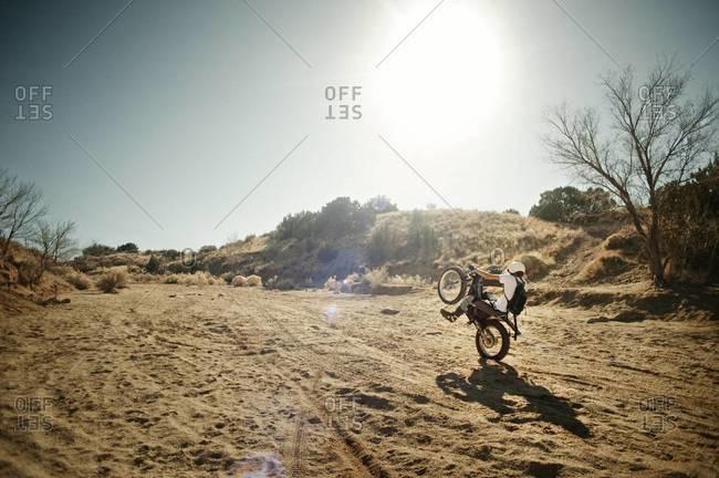 Trials motorbiker doing a wheelie in desert