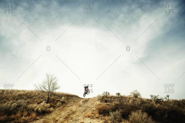 Motorcyclist jumping in desert