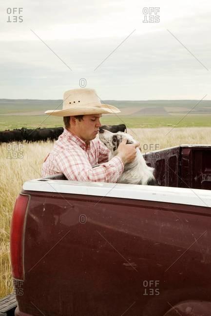 Rancher kissing his Australian shepherd