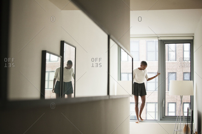 Woman standing on the windowsill at an apartment