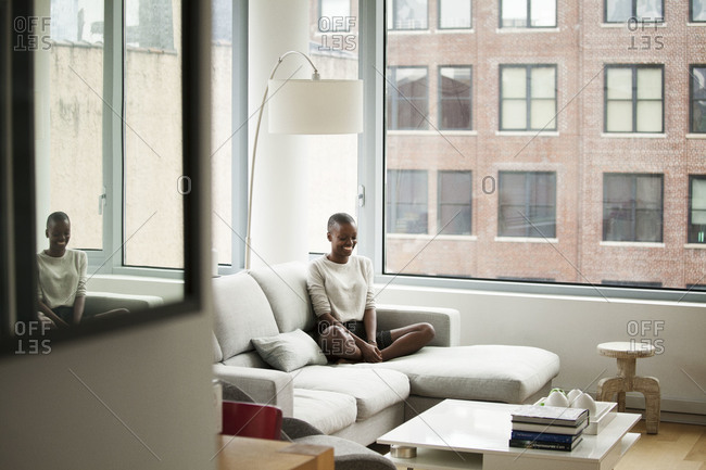 Woman sitting and smiling on the couch at an apartment