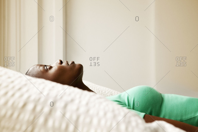 Profile of woman staring at the ceiling in the bedroom