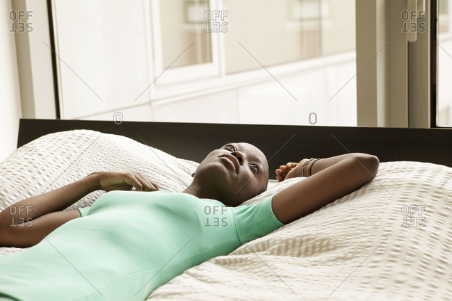 Woman thinking lying on bed