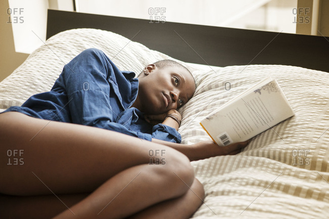 Woman curled up in bed reading a book