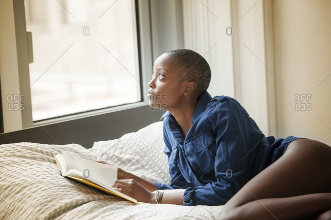 Woman holding a book in bed