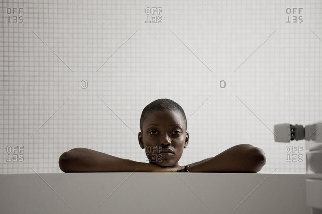 Close up of woman leaning on the ledge of a bathtub