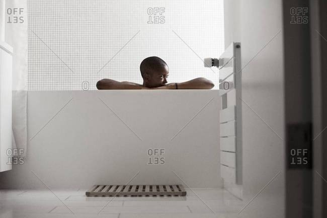 Woman leaning on the ledge of a bathtub