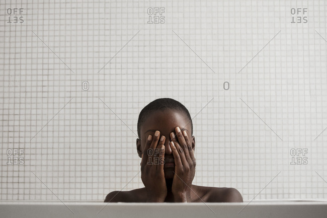 Woman covering her face in the bathtub