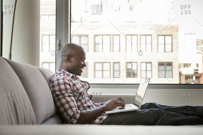 Man using his laptop at home on couch