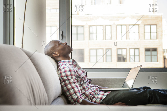 Man taking a break from working on his laptop