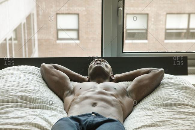 Shirtless African American man lying down