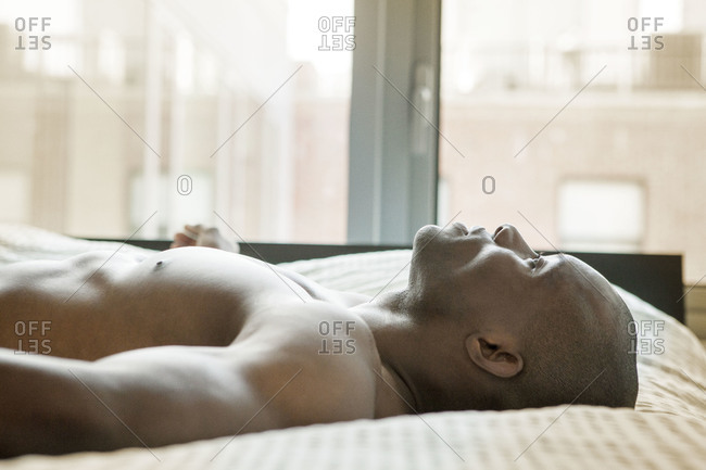 Profile of shirtless African American man lying in bed